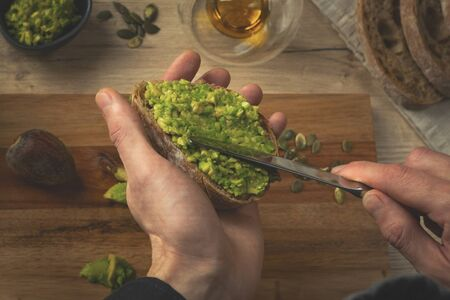 Close up of a chef hands making avocado sandwich on a wooden table. Toast with hummus. Man making breakfast in the kitchen. Reklamní fotografie