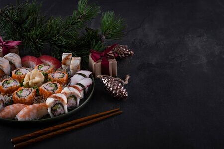 Assorted sushi sashimi set with salmon, tuna and eel on dark slate background with decorations. Christmas or New Year background. Tree branch with gifts. Traditional japanese food. Copy space for text