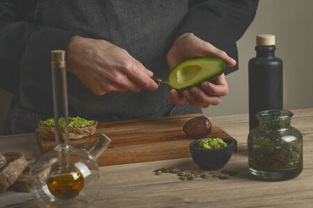 Chef making avocado sandwiches with bread, nuts, herbs and avocado oil on a wooden table. Man making breakfast in the kitchen. Healthy food preparation. Toned faded background