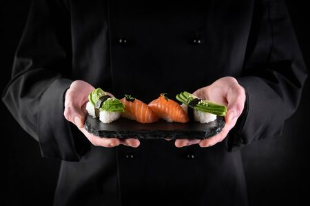 Sushi served on stone slate in chef hands on dark background. Decorated sashimi nigiri with salmon and avocado. Traditional japanese food. Copy space for text Reklamní fotografie