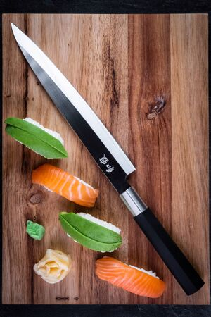Sushi set with knife on wooden board with dark background. Sashimi nigiri with salmon and avocado. Japanese traditional food. Top view, copy space for text