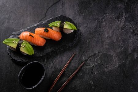 Sushi set on dark stone slate background. Decorated sashimi nigiri with salmon and avocado with soy sauce and chopsticks. Traditional japanese food. Close up with copy space for text Reklamní fotografie
