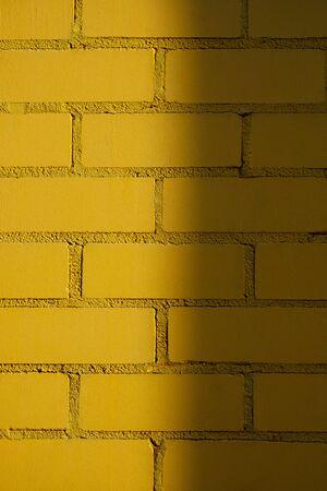 Yellow sunny brick wall texture background. Half shaded beautiful new bricks. Vertical, close up