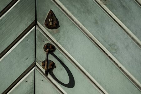 Old medieval wooden door detail in sunlight. Green wooden door with rusty lock and handle. Abstract pattern wooden texture background. Green triangle pattern. Close up, copy space 免版税图像