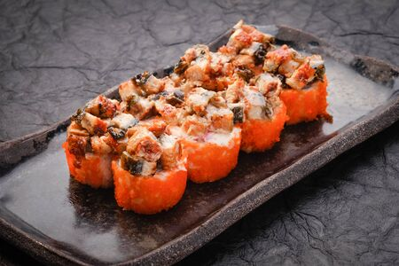 Sushi set served on black plate on dark background. Baked maki roll with eel, masago, salmon, cream cheese, avocado and prawn. Assorted sushi. Japanese food. Restaurant menu. Side view, close up