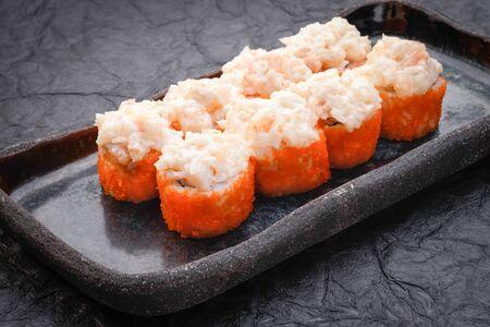 Sushi set served on dark background. Baked maki roll, Philadelphia maki with masago, salmon, cream cheese, avocado and prawn. Assorted sushi. Japanese food. Restaurant menu. Side view, close up