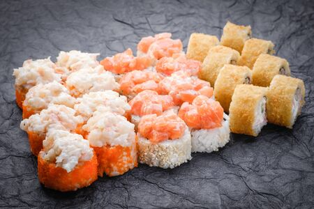 Sushi set served on dark background. Baked maki roll, Philadelphia maki, tempura maki with salmon, cream cheese, avocado and prawn. Assorted sushi. Japanese food. Restaurant menu. Side view, close up Stock Photo