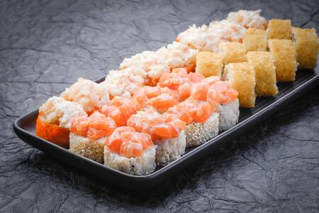 Sushi set served on black plate on dark background. Baked maki roll, Philadelphia maki, tempura maki with salmon, cream cheese, avocado and prawn. Japanese food. Restaurant menu. Side view, close up