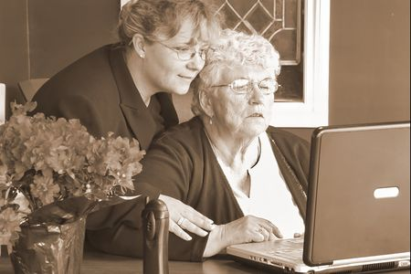 Working side by side. Granddaughter and Grandmother in an office setting Stock Photo