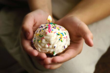 hoping: A young childs hands holding a special birthday cupcake.