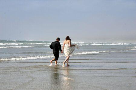 bride and groom on ocean beach