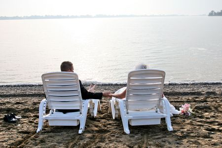 bride and groom sitting at the beach Archivio Fotografico