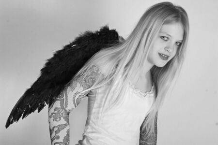 bad gothic teenage angel with tattoo on her arms photo