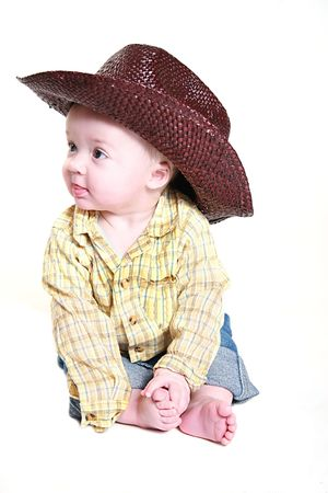 Little cowboy sitting on the floor playing with his toes Stock Photo