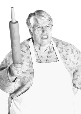 A very upset grandmother shaking her rolling pin. She has flour on her face from baking.