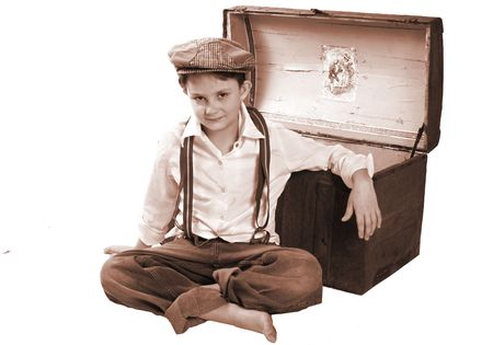 A child sitting up by a treasure chest for a portrait.