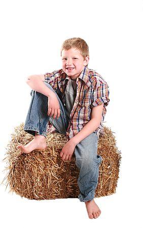jongen zittend op een baal hooi.