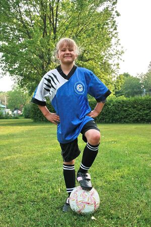 sports kid posing with a soccer ball