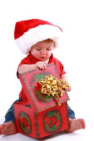 Tiempo de Navidad, muchacho que abre sus presentes.