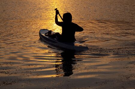 silhouette of a young boy sea kayaking at sunset Archivio Fotografico