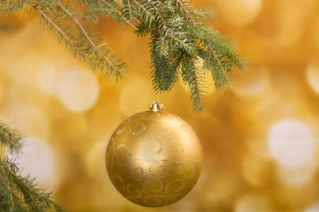 Gold christmas decoration with tree lights glimmering in background
