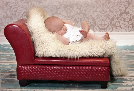 newborn baby posing in his sleep like a Couch Potato. Bright red couch and vintage wallpaper  add  to this portrait.