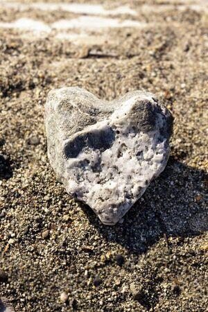 heart of stone: A rock shaped like a heart  With a sand background