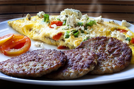 Hot breakfast with an Omelette and fried sausage rounds  Stock Photo