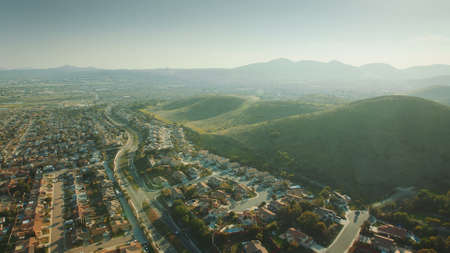 Aerial Flying over California Suburb. Aerial Landscape View For City and Mountain. Фото со стока