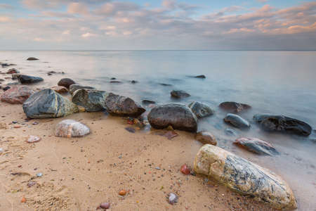 Beautifu rocky sea shore at sunrise or sunset. Long exposure landscape. Baltic sea near Gdynia in Poland. Standard-Bild