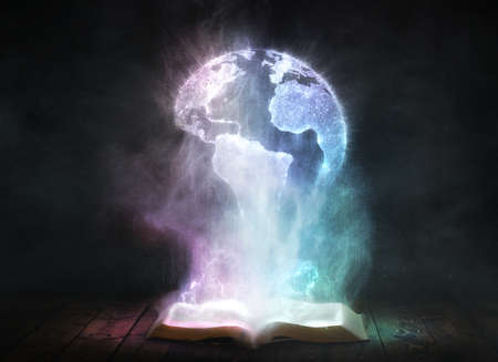 An open dusty Bible with the shape of the earth in the particles Foto de archivo