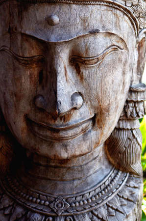 Wooden Figure of Buddha head and in meditation  photo