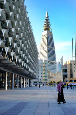 January 25 2017 - Riyadh, Saudi Arabia: A Man walks nearby the Saudi National Museum park and Al Faisaliyah Center Tower in the background along Olaya Street area. Redakční