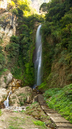 Waterfall on the way to Annaourna circuit, covered with green bushes and trees Tal Nepal Stock Photo