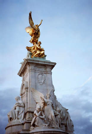 buckingham palace: Golden statue of a winged woman, part of the sculpture of Queen Victoria in Buckingham Palace Stock Photo