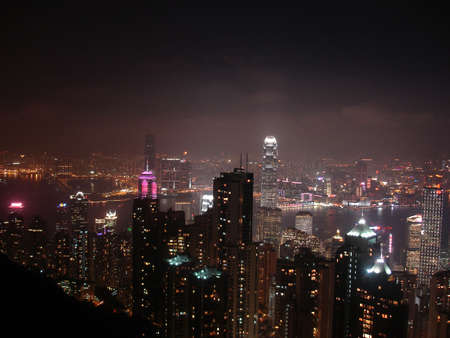 A panoramic view of Hong Kong, Kowloon and Victoria Harbour from Victoria Peak at night                               photo