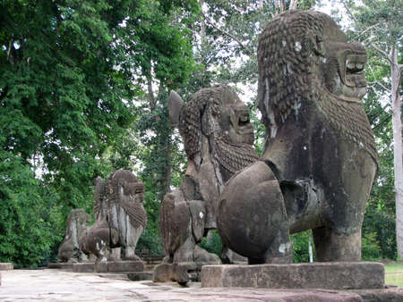 Statue of a lion guards the stairs on the central pyramid at Bakong of Roluos Group, Angkor, Cambodia photo