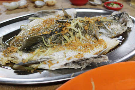 Chinese style steamed fish with soy sauce photo