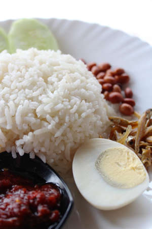 Nasi lemak served with anchovies, peanuts, egg, cucumber and sambal belacan