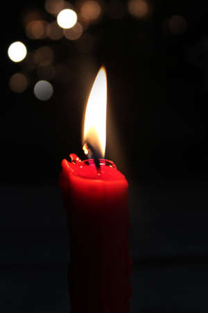 A single burning red candle photo