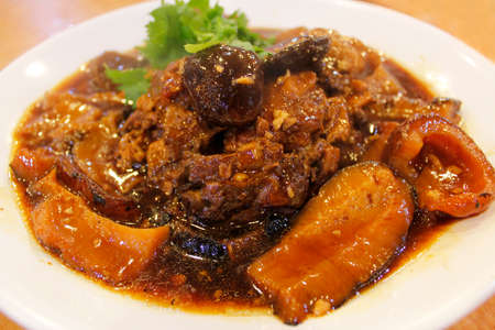 Braised sea cucumber with pork trotters and mushrooms in soy sauce Stock Photo