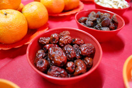 The dried crimpled skin Chinese red dates with dried Longan, lotus seed and oranges are displayed in Chinese New Year s prayer ceremony at midnight