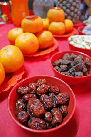The dried crimpled skin Chinese red dates with dried Longan, lotus seed and oranges are displayed in Chinese New Year s prayer ceremony at midnight photo