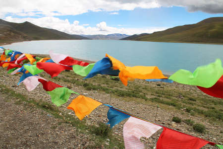 Yamdrok Lake and the prayer flags in windy day, Tibet, China