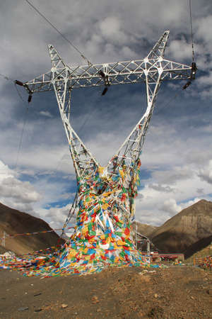 Power transmission tower with the prayer flags in Tibet, China photo