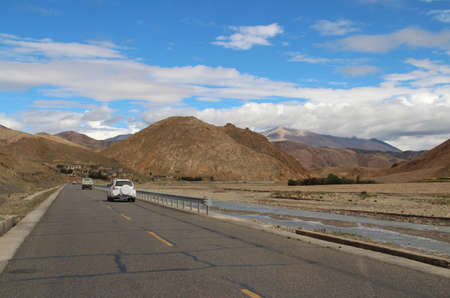 Road running through mountains and Tibetan village in Tibet, China