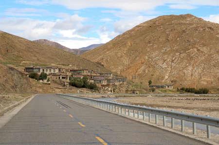 Road running through mountains and Tibetan village in Tibet, China photo