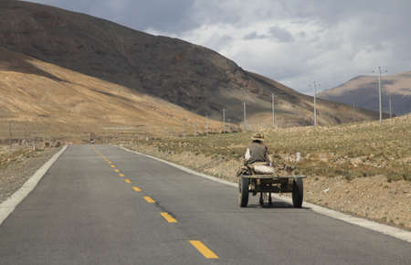Tibetan farmer ride the horse car on the road running through mountains in Tibet, China