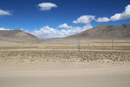 View of the mountain and sand dune with dirt road in Tibet, China Stock Photo
