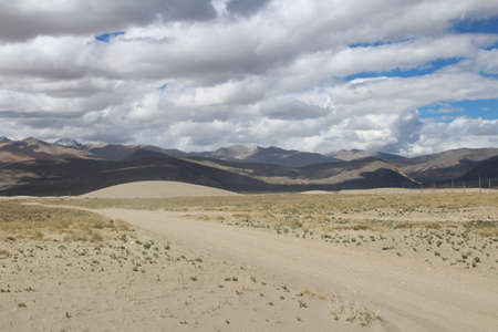 View of the mountain and sand dune with dirt road in Tibet, China photo